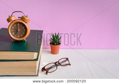 Books And Glasses On A White Wooden Table Are Clocks And Decorations