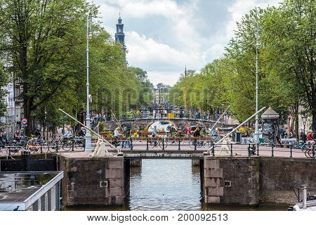 Amsterdam the Netherlands - 13 August 2017: people crossing bridges on the Prinsengracht with westerkerk in background