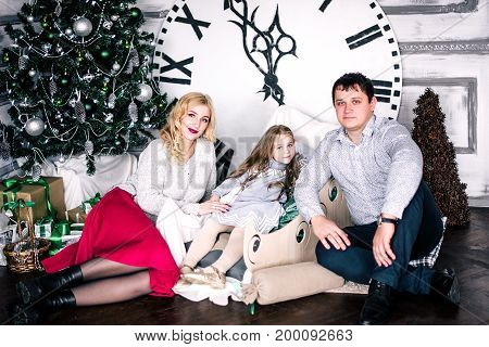 Family Gathering Together Near The Christmas Tree. The Clock In The Background Show Five Minutes To