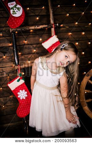 Baby Girl 4-5 Year Old Posing In Room Over Christmas Tree With Decorations. Looking At Camera. Merry