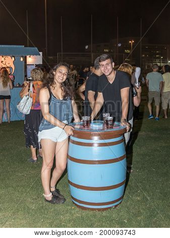Haifa Israel August 16 2017 : A young couple happily posing near a decorative beer cask at the traditional annual beer festival in Haifa Israel