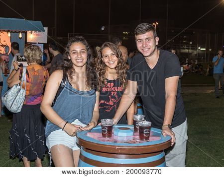 Haifa Israel August 16 2017 : Young people joyfully posing near a decorative beer cask at the traditional annual beer festival in Haifa Israel