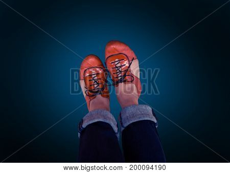 Digital composite of red shoes on feet with blue background