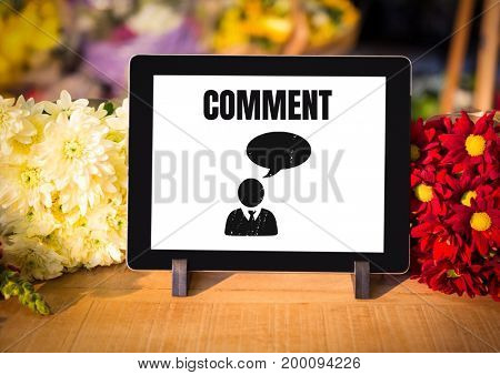 Digital composite of Comment text and chat graphic on tablet screen with flowers