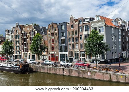 Amsterdam the Netherlands - 13 August 2017: traditional dutch houses lining street on canal