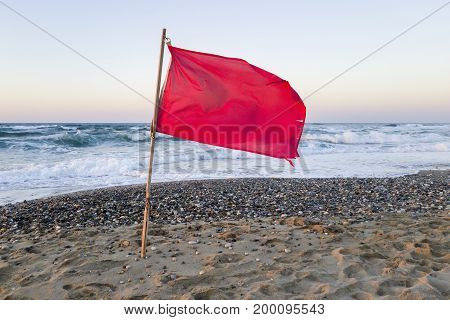 Red flag with blowing wind beside Crete shore, to signal that it is not safe to swim in the sea.