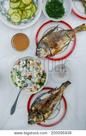 Fried Dorado fish, lettuce and vegetables on the table