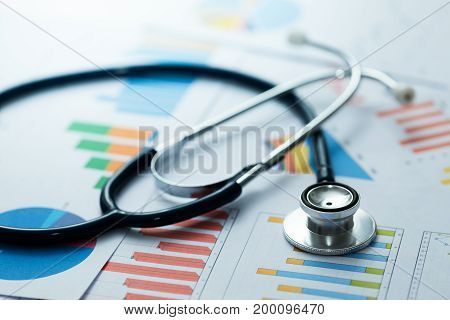 medical statistics and graphic charts with stethoscope