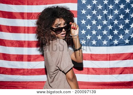 Image of serious african young lady wearing sunglasses standing over USA flag. Looking camera.