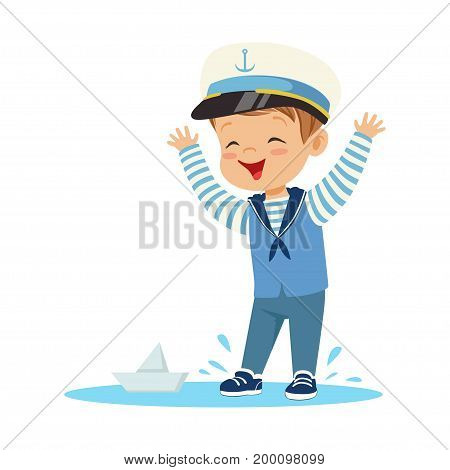 Cute smiling little boy character wearing a sailors costume standing in a puddle playing with paper boat colorful vector Illustration on a white background