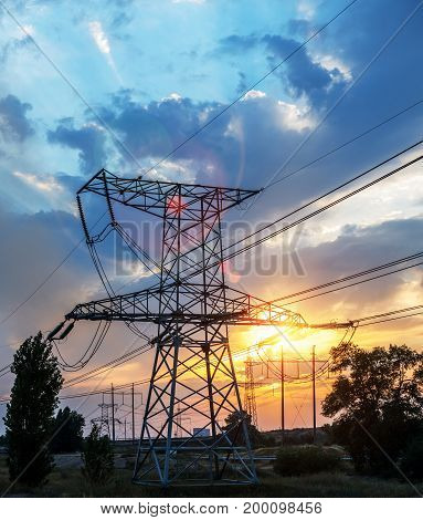 high-voltage power lines at sunset. electricity distribution station.