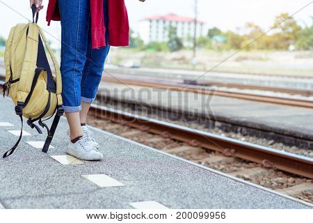 A Walking young girl tourist on side railway holding smartphone with backpack going to travel scenery town tour around at train station platform for take the rest happy and life experience having fun