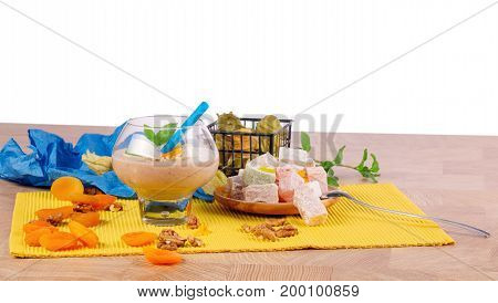 A glass of cocktail, green leaves of mint, orange dried apricots, walnuts, a wooden plate of Turkish delight, rahat lokum or turkish delight, silver spoon on a wooden table and isolated on a white background.