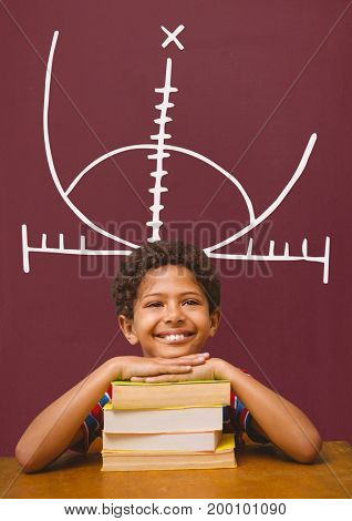 Digital composite of Happy student boy at table against red blackboard with education and school graphic