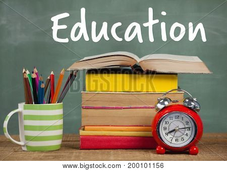 Digital composite of Books on Desk foreground with blackboard Education text