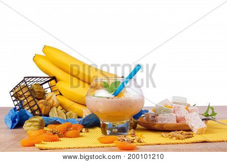 A wooden table with a plate of rahat lokum, a glass of cocktail with walnuts, yellow bananas, orange dried apricots and green leaves of mint, bright physalis and a spoon isolated on a white background.