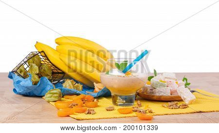 A wooden table with physalis, yellow bright bananas, a glass of cocktail with walnuts and dried apricots, sappy mint leaves, physalis, lokum isolated on a white background.