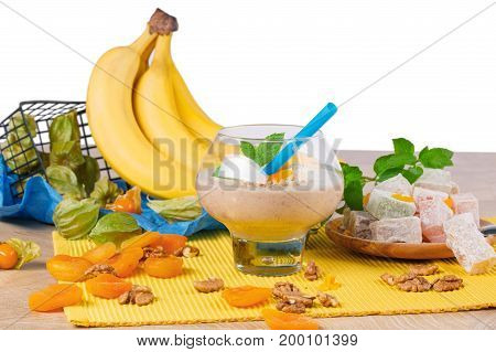 A wooden table with yellow bright bananas, a glass of cocktail with walnuts and dried apricots, sappy mint leaves, physalis, Turkish delight isolated on a white background.