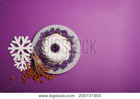 Top view of a plate with a round cake covered with powdered sugar and decorated with little flowers, almond, sticks of cinnamon and white snowflakes on a bright violet background, copy space.