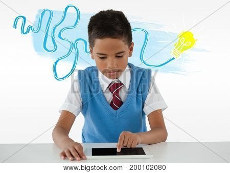 Digital composite of Schoolboy on tablet with colorful idea light bulb doodle