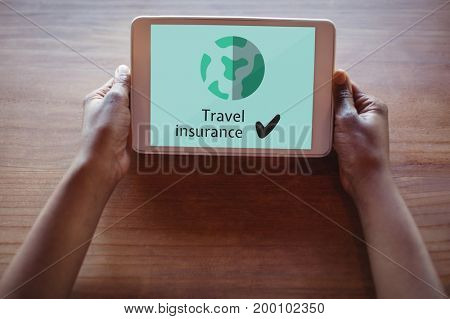 Digital composite of Person holding a tablet with travel insurance concept on screen