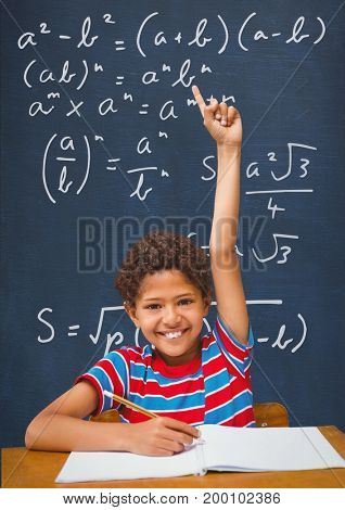 Digital composite of Happy student boy at table raising hand against blue blackboard with education and school graphics