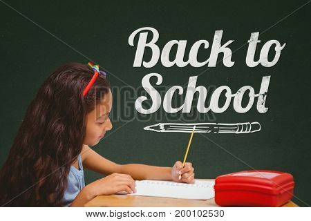 Digital composite of Student girl at table writing against green blackboard with back to school text