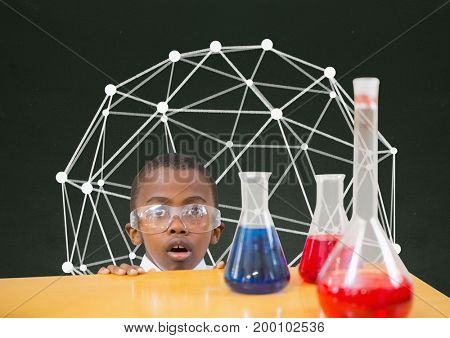 Digital composite of Surprised student boy at table against green blackboard with education graphic