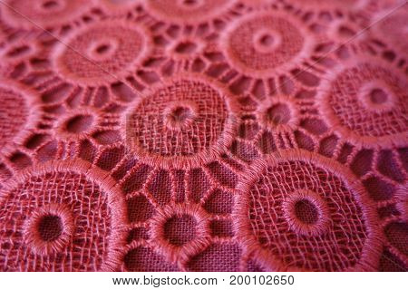 Close up of pink open embroidery with circular eyelets