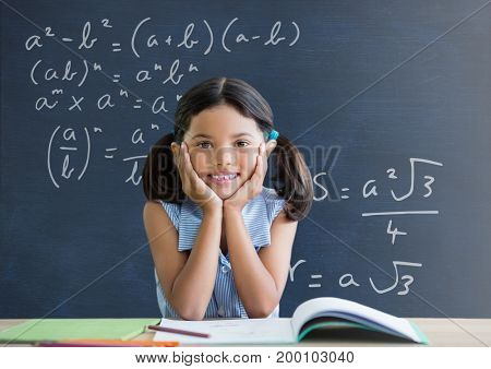 Digital composite of Student girl at table against blue blackboard with education and school graphics