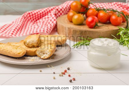 Organic cherry tomatoes with rosemary swedish toasts and cream cheese on rustic wooden table