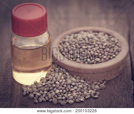Seeds of Cannabis or hemp with essential oil in bottle on wooden surface