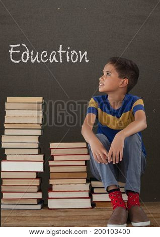 Digital composite of Student boy sitting on table against grey blackboard with education text