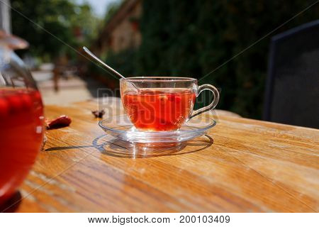 A beautiful cup full of red herbal tea on a wooden table. Strawberry tea in a kettle and a teacup on a blurred sunny street background. Black tea with strawberries at the outside cafe. Copy space.