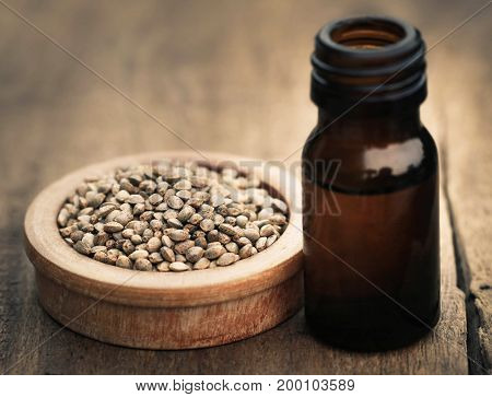 Seeds of Cannabis or hemp with essential oil in bottle on timber surface