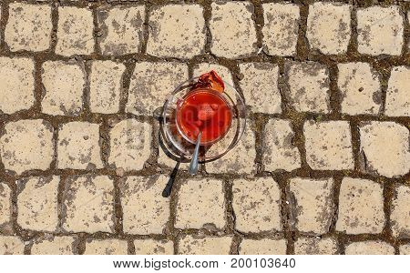 A view from above on a full, small teacup on a spacious wall background. A mug of black tea with strawberries and spices. Light red, medical tea with a carnation flower and long spoon. Copy space.