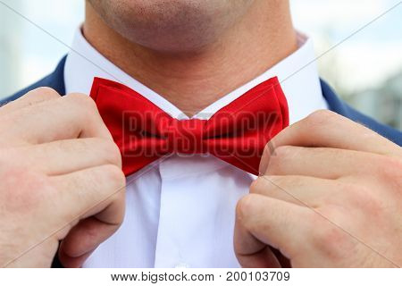 men's hands are readjusting red bow tie