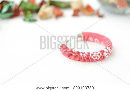 Red Beaded Bracelet With Floral Print On A Textile Background