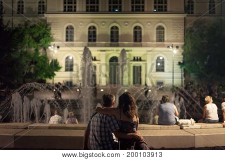 SZEGED HUNGARY - JULY 22 2017: Lovers in front of the Fountain on Dugonics Ter Square at night in summer. This square and the university building on it are symbols of the city