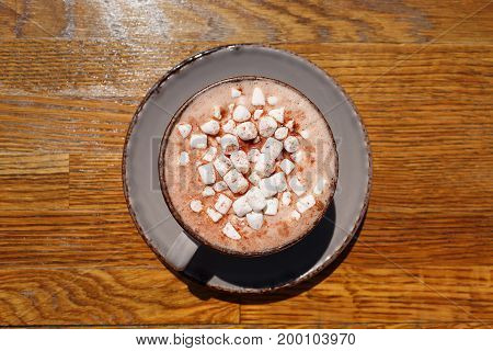 A macro picture of a gray porcelain coffee cup filled with hot cappuccino and little white marshmallows. Warming sweet beverage on a wooden table background. Cafe, breakfast, brunch concept.