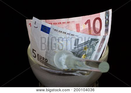 Euro notes in a glass mortar with a pestle.
