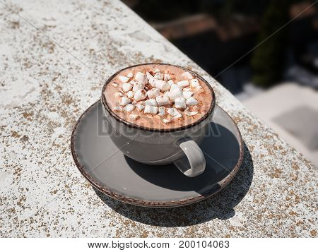 A view from above on a gray porcelain mug full of hot chocolate with marshmallows. Sweet cappuccino on a stone background. A cup with a round plate. Copy space. Relaxation, breakfast concept.