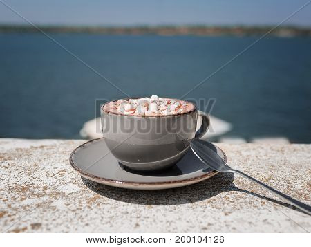 A close-up picture of a gray porcelain mug of hot chocolate with marshmallows. Sweet cappuccino on blurred sea background. A cup with a metal spoon. Copy space. Relaxation, breakfast concept.