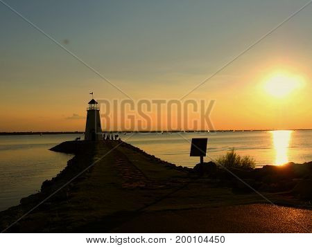 A lighthouse silhouetted by a beautiful sunset, with silhouettes of people around