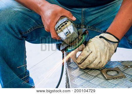 Worker Using Angle Grinder In Factory And Throwing Sparks. Electric Grinder Metal With Worker Cuttin