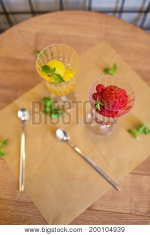A view from above on refreshing sorbet scoops on a wooden table background. Two portions of bright juicy ice cream in crystal glasses. Summer desserts with decorative mint leaves. Copy space.
