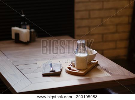 A close-up of beautiful lunch composition. A healthy salad with creamy sauce and a nutritious milkshake on a wooden table. A set of organic dishes and a spoon on a blurred background. Copy space.