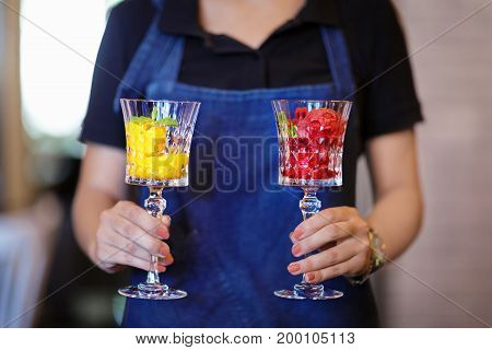 Close-up picture of two portions of bright ice cream scoops in crystal glasses. Refreshing sorbet in female hands. Cool summer desserts with decorative mint leaves. Tasty frozen juice. Copy space.