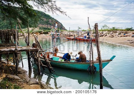 2 Fisherman are gathering and choosing mussel shell on their small fishing boat