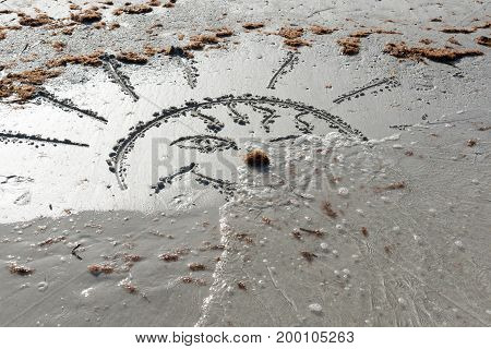 The waves wash away the sun drawn on the sand. Farewell Summer!